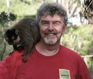 Ged Caddick in Madagascar with a lemur on his back